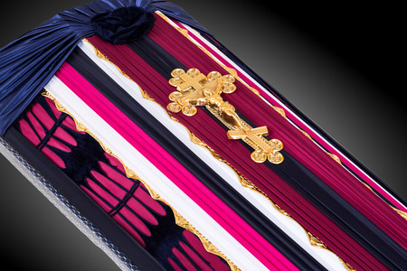 closed coffin covered with pink and blue cloth decorated with Church gold cross on gray luxury background. Close-up.