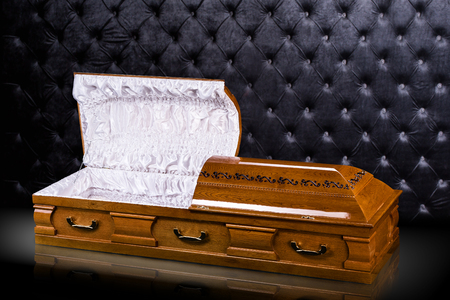 Opened wooden brown sarcophagus isolated on gray luxury background. casket, coffin on royal background.