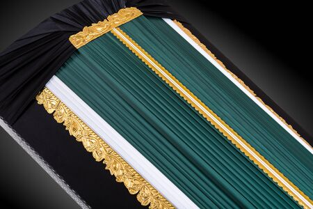 closed dark green coffin covered with elegant cloth isolated on gray background. coffin close-up.