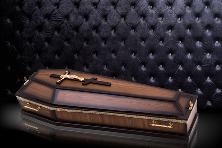 closed wooden brown coffin with Church cross isolated on gray luxury background. casket on royal background.