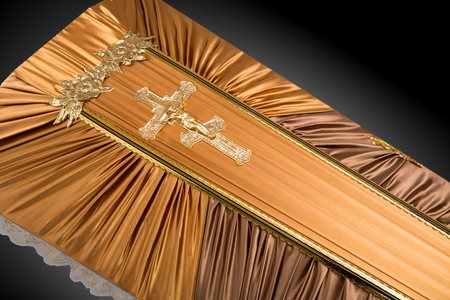closed beige coffin covered with cloth isolated on gray background. coffin close-up with gold Church cross on royal background. Ritual objects for burial. Surrender body dust of the earth. Christian funeral ritual Stock Photo