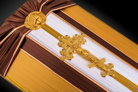 closed coffin covered with brown and beige cloth decorated with Church gold cross on gray luxury background. Close-up.