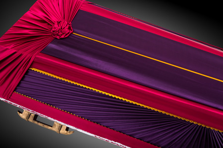 closed red and purple coffin covered with elegant cloth isolated on gray background. coffin close-up.