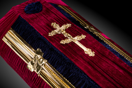 closed red velvet coffin covered with cloth isolated on gray background. coffin close-up with gold Church cross.