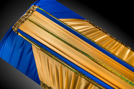 closed coffin covered with elegant cloth isolated on gray background. coffin close-up with gold flowers.