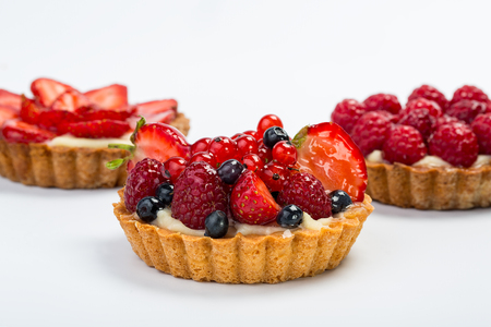 bake sale: Three Fresh Fruit Tarts with berries isolated on white background.