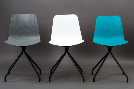 greengrass: Row of three color plastic chairs isolated on gray background. Furniture series.