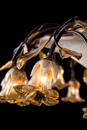 resplandor: Classic chandelier in flower style isolated on black background. Close-up