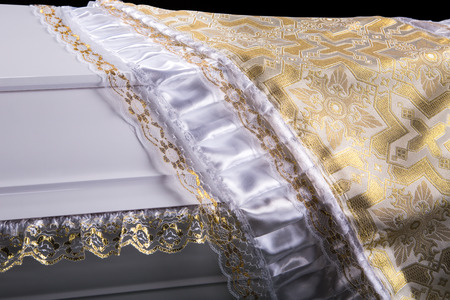 closed wooden white coffin covered with white ritual blanket isolated close-up. Stock Photo