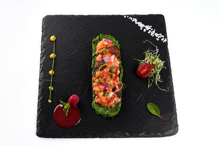 fresh salmon tartar with salt and herbs, studio shot. Fish tartar on black shale. On white background