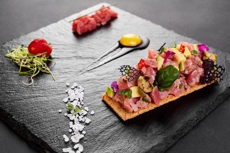 fresh tuna tartar with salt and herbs, studio shot. Fish tartar on black shale. Stock Photo