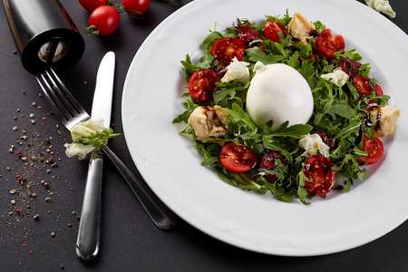 Fresh vegetable salad in white plate on black. Healthy salad with Sun dried tomatoes, Arugula, Mozzarella and Balsamic. Stock Photo