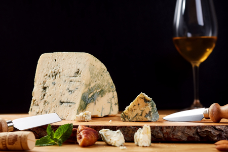 Slice of French Roquefort cheese with mint. Blue cheese in wooden board.
