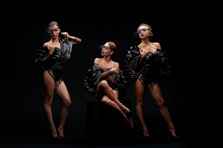 Beautiful sexy go-go performers isolated on black. Sexy girl dance group posing in black underwear