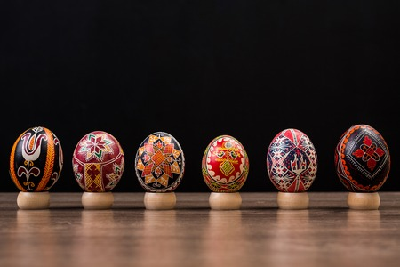 Pysankas in a row, decorated Easter eggs on black background.