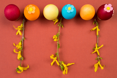 Painted Easter eggs in a row, decorated Easter eggs and yellow branches on color background. Stock Photo