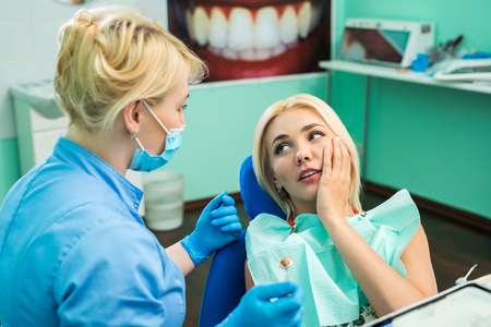 Young woman at the dentist complaining about a toothache. Dentistry. Doctor and the patient Stockfoto