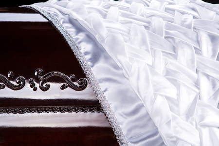 closed wooden brown coffin covered with white ritual blanket isolated close-up.