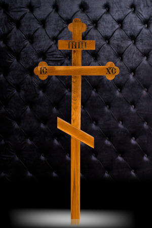 Brown wood Cross tombstone isolated on dark luxury background. Ritual object for burial Stock Photo