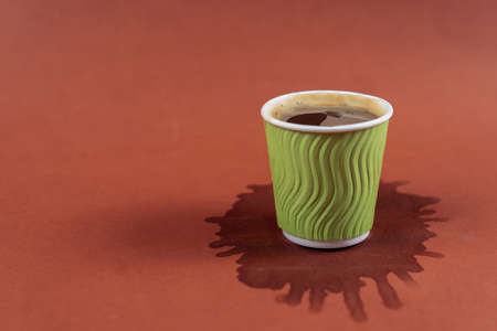 Coffee in green paper cup on brown background with stain. Spilled espresso on table. Glass with americano on coffee stain. Spilled drink under cup of coffee in cafe. Coffee shop concept. Archivio Fotografico - 155322308