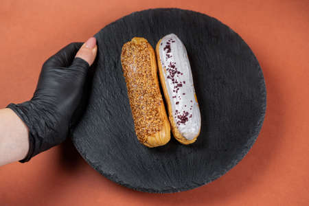 Raspberry and caramel eclair on round black rock stand held by hand in black glove. Eclairs with glaze in cafe. View from above. Cake with choux cream on slate stand. Tasty dessert concept. 版權商用圖片 - 155363647