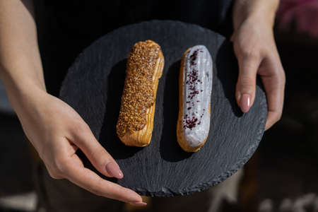 Raspberry and caramel eclair on round black rock stand in hands. Two eclairs with white and brown glaze in cafe. Cake with choux cream on slate stand. Tasty dessert concept.