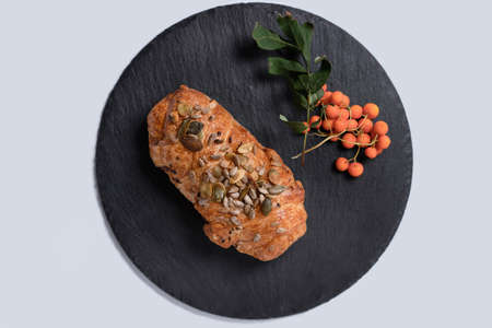 Meat pie with seeds and sprig of rowan on round black rock stand on white background. View from above. Baking to order concept. Turkey bun sprinkled with seeds in cafe. Quick snack concept.