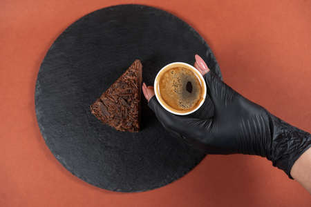 Chocolate cake on round black rock stand and coffee in hand in glove. Confectionery concept. Cake with chocolate chip and espresso on slate stand. Tasty dessert concept. View from above. 版權商用圖片 - 155363675