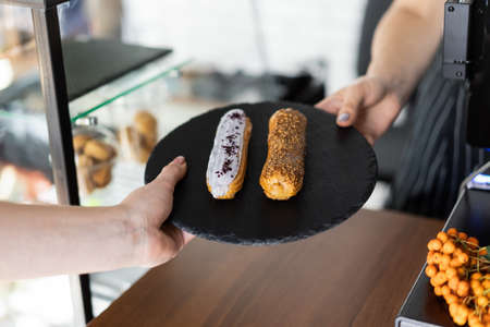 Raspberry and caramel eclair on round black rock stand in hands. Seller gives order to buyer. Sweets to order concept. Two eclairs with white and brown glaze in cafe. Tasty dessert concept. 版權商用圖片 - 155363751