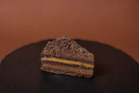 Chocolate cake on brown round stand. Confectionery concept. Cake with chocolate chip. Tasty dessert concept. Piece of brownie in cafe. Sweets to order concept. 版權商用圖片 - 155545842