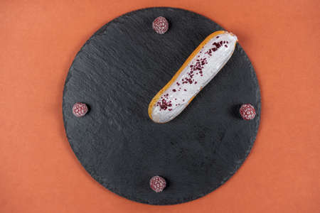 Raspberry eclair on round black rock stand on brown background. Eclair with white glaze and raspberries in cafe. View from above. Cake with choux cream and pink berries. Tasty dessert concept. 版權商用圖片 - 155884543
