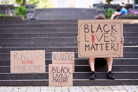 Kiev, Ukraine - July 31 2020: Black Lives Matter posters near man sitting on the stairs. Stop racism concept. Black Lives Matter protest sign. Action against discrimination by skin color.