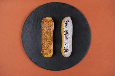 Raspberry and caramel eclair on round black rock stand on brown background. Two eclairs with glaze in cafe. View from above. Cake with choux cream on slate stand. Tasty dessert concept. 版權商用圖片