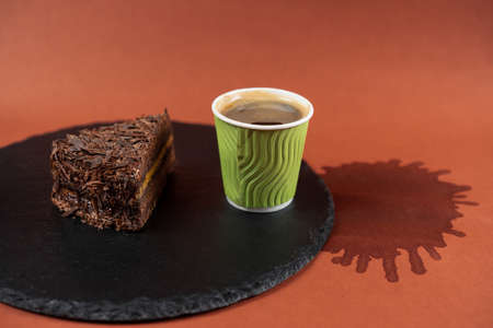 Chocolate cake and coffee in green paper cup on black rock stand on coffee stain background. Cake with chocolate chip on slate stand and spilled coffee. Piece of brownie and espresso. 版權商用圖片 - 155660861