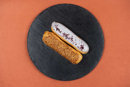 Raspberry and caramel eclair on round black rock stand on brown background. Eclairs with white glaze in cafe. View from above. Cake with choux cream on slate stand. Tasty dessert concept. 版權商用圖片 - 155884567