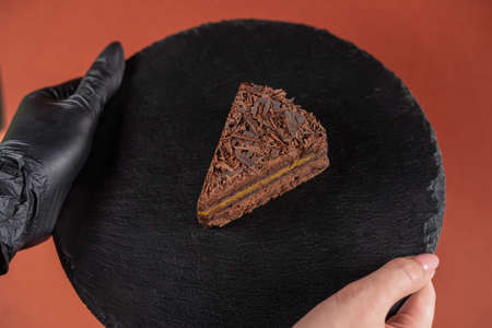 Chocolate cake on round black rock stand in hands. Confectionery concept. Cake with chocolate chip on slate stand held by hand in black glove.Tasty dessert concept. Sweets to order concept.