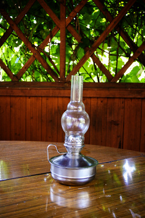 old kerosene lamp on the table outdoor gazebo with greens photo