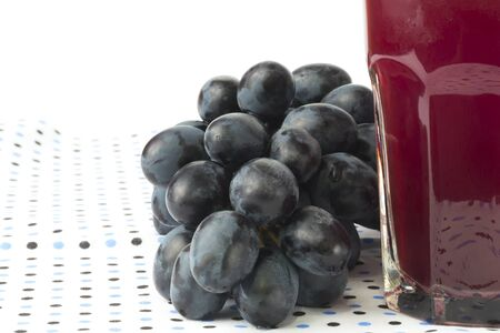 Dark grapes Isolated on white background glass of juice photo