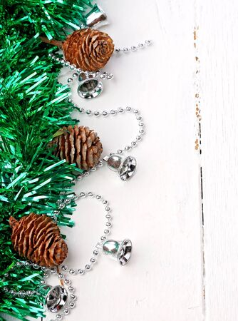 silver bells: Christmas a holiday decoration fir background rustic old cones tinsel winter white wooden retro vintage Garland of silver bells Stock Photo