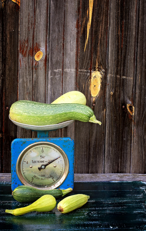 courgettes: vintage scales courgettes on dark wooden background rustic farm products
