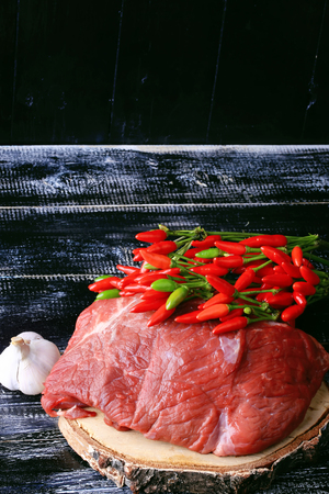 circular muscle: raw fillet of beef with hot peppers on dark wood background retro style