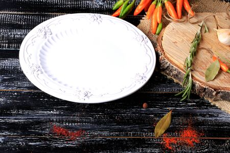 grunge cutlery: empty white plate hot peppers on a dark old wooden background spices retro vintage style