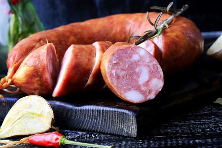 krakow sausage: smoked homemade sausage sliced spices pepper garlic rosemary dark wooden background rustic style retro vintage