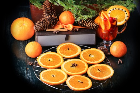 solemnity: Christmas composition of preparation for drying oranges hot drink with cinnamon, anise tangerine cranberry fir vintage style on old wooden background
