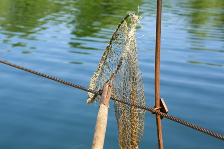marinelife: vintage landing net to catch fish on the river selective focus Stock Photo