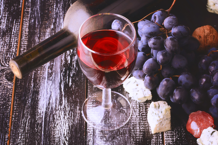des vins: glass of wine grapes alcohol bottle cheese worn wooden background retro vintage style