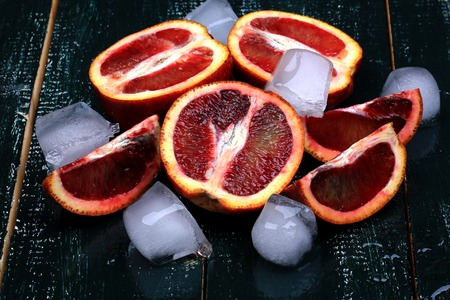 burgundy colour: red juicy oranges with ice on a dark wooden background for summer refreshing drink