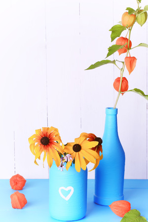 a rural community: Autumn rural Community Decor handmade glass jar and a bottle of colored paint with autumn flowers on a wooden background Stock Photo