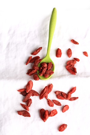 lycii: goji berries in a spoon on a white linen background