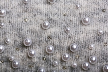 Knitted background. Light gray gentle wool background pattern. Background embroidered with beads Archivio Fotografico